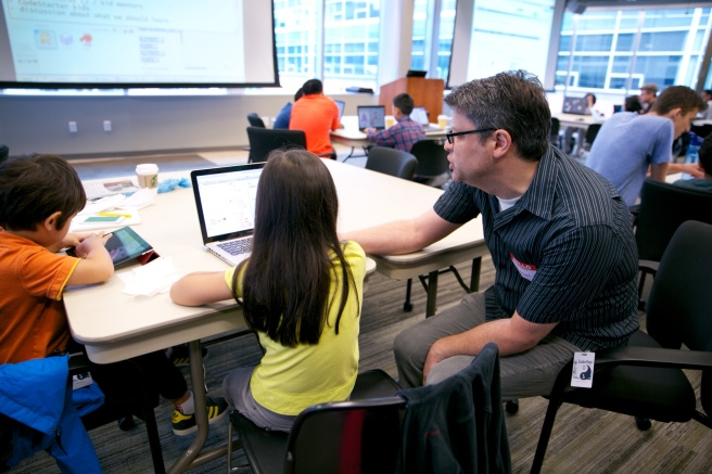 A Seattle CoderDojo mentor helps Meilee with a series of commands.